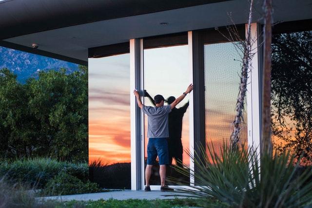 Osoba drží dvere, sklenená výplň, exteriér