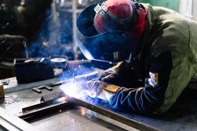 Muž zvára kusy ocele