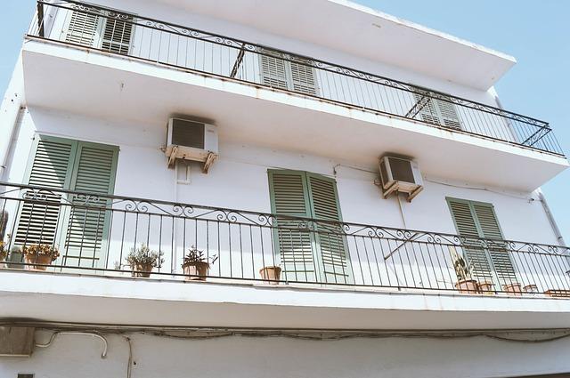 Biely dom s dlhým balkónom so zábradlím.jpg
