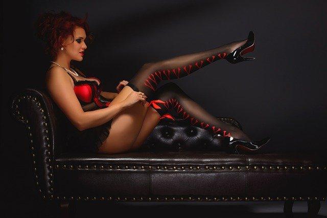Žena v červeno-čiernom erotickom oblečení sedí na gauči.jpg