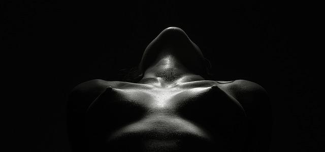 Žena v tme s nahým poprsím a zaklonenou hlavou.jpg