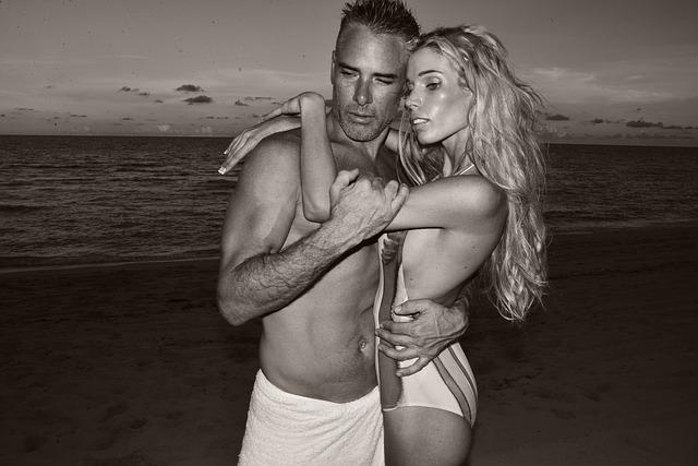 Muž a žena v objatí na pláži, čiernobiele.jpg