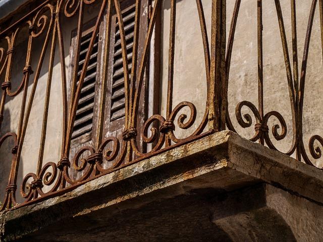 Detail na staré zhrdzavené zábradlie na betónovom balkóne.jpg