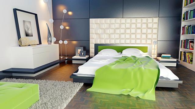 Manželská posteľ, na ktorej je prehodená zelená deka.jpg