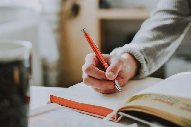 Človek v svetri píše poznámky do zápisníka