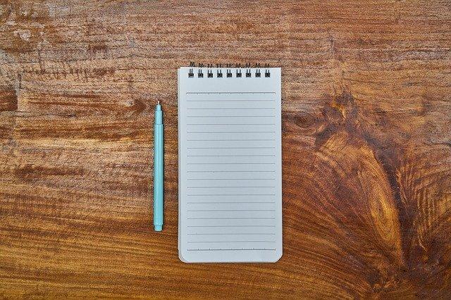 Poznámkový blok a tyrkysové pero na hnedom stole